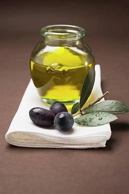 Black Olive Photograph - Olive Sprig With Black Olives, Jar Of Olive Oil Behind by Foodcollection