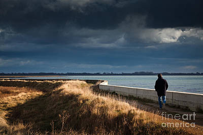 One Man Walking Alone By Sea Wall In Sunshine On Dramatic Stormy Art Print