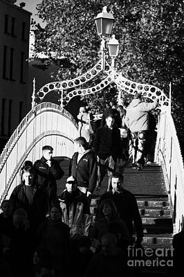 Hapenny Photograph - People Crossing The Hapenny Ha Penny Bridge Over The River Liffey In Dublin At A Busy Time Vertical by Joe Fox