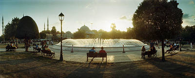 People Sitting At A Fountain With Blue Art Print by Panoramic Images