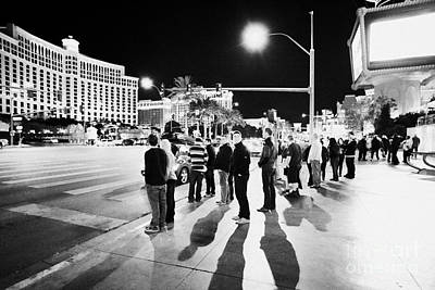 Crosswalk Photograph - People Waiting To Cross Las Vegas Boulevard Outside The Bellagio And Paris At Night Nevada Usa by Joe Fox