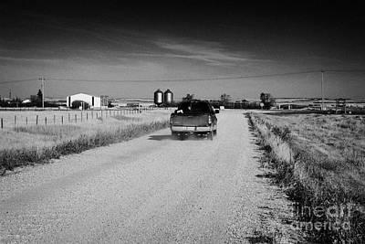 pickup truck driving down rough unpaved rural road in farming community Saskatchewan Canada Art Print by Joe Fox