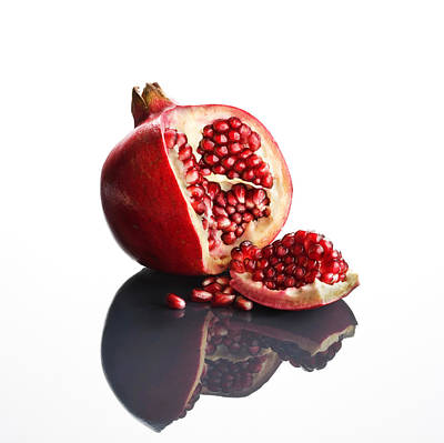 Food And Beverage Royalty-Free and Rights-Managed Images - Pomegranate opened up on reflective surface by Johan Swanepoel
