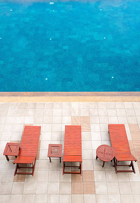 Swim Ladder Photograph - Poolside Deckchairs Alongside Blue Swimming Pool by Jirawat Cheepsumol