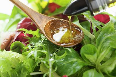Pouring Olive Oil Into Wooden Spoon Above Salad Leaves Art Print