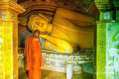 praying buddhist monk by a lying buddha in Sri Lanka Art Print by Gina Koch