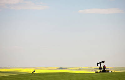 Photograph - Pumpjack In Canola Field In Rural by Imaginegolf