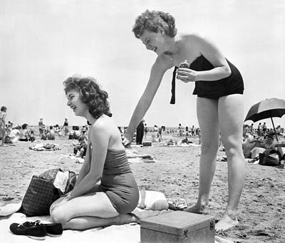 Beach Scenes Photograph - Putting On Sun Tan Lotion by Underwood Archives