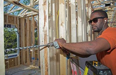 Helping Photograph - Re-building After Hurricane Katrina by Jim West