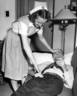 Laying Down Photograph - Red Cross Nurse With Patient by Underwood Archives