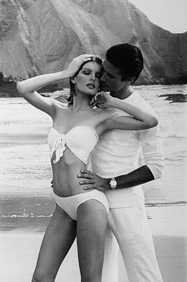 Fashion Photograph - Rene Russo Posing With A Male Model On A Beach by Francesco Scavullo