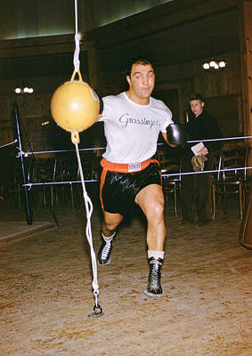 Striking Photograph - Rocky Marciano Striking Bag by Retro Images Archive