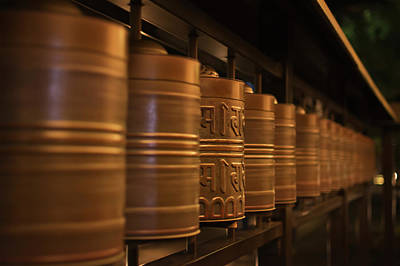 National Past Time Photograph - Row Of Spinning Prayer Wheels At Night by Philippe Widling