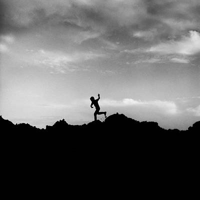 Running Boy Silhouetted Against Dramatic Sky Art Print