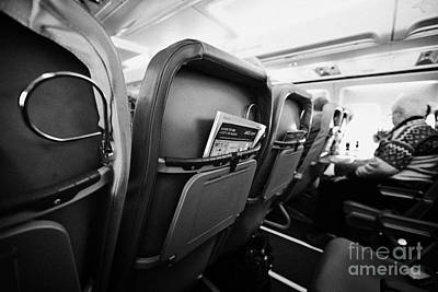 Passenger Plane Photograph - Safety Card And In Flight Magazine In Seat Pocket Interior Of Jet2 Aircraft Passenger Cabin In Fligh by Joe Fox