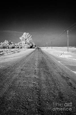 Harsh Conditions Photograph - salt and grit covered rural small road in Forget Saskatchewan Canada by Joe Fox