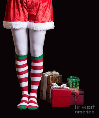 Elf Photograph - Santas Elf Legs Next To A Pile Of Christmas Gifts Over Black by Edward Fielding