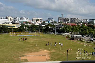 Schoolchildren Practicing On Playing Field With Singapore Skyline In Background Original