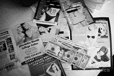 Prostitution Photograph - selection of leaflets advertising girls laid out on a hotel bed with us dollars cash in Las Vegas Ne by Joe Fox