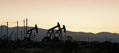 Oil Pump Photograph - Silhouette Of Oil Rigs At Sunset by Panoramic Images