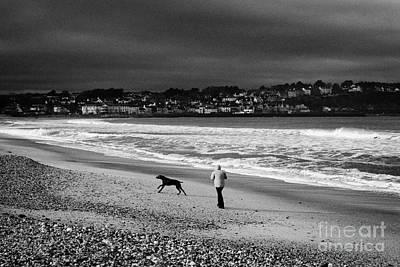Single Woman Out Walking Her Dog On Ballycastle Beach In Winter County Antrim Northern Ireland Art Print by Joe Fox