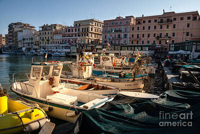 small working fishing boats moored stern first in Anzio harbour Art Print