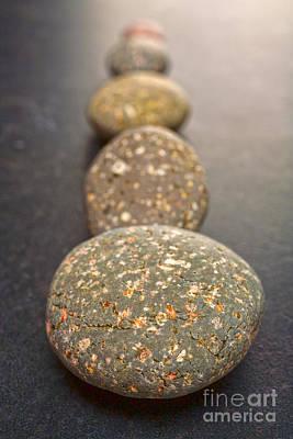 Straight Line Of Speckled Grey Pebbles On Dark Background Art Print