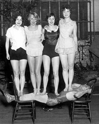 Reclining Chairs Photograph - Strongman Holds Up Actresses by Underwood Archives