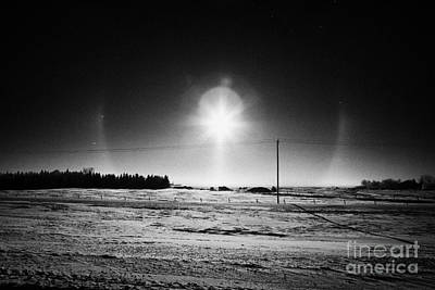 Phantom Dog Photograph - sun dog parhelion halo due to ice crystals surrounding the sun in Saskatchewan Canada by Joe Fox