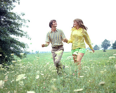 Teenage Girl Photograph - Teenage Boy And Girl Running In Meadow by Vintage Images