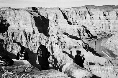 teenage boys standing looking into the grand canyon and colorado river guano point Grand Canyon west Art Print by Joe Fox