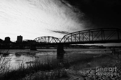 the old traffic bridge over the south saskatchewan river in winter flowing through downtown Saskatoo Print by Joe Fox