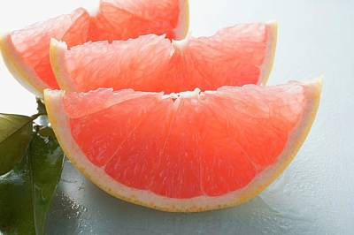 Grapefruit Photograph - Three Pink Grapefruit Wedges, Leaves Beside Them by Foodcollection
