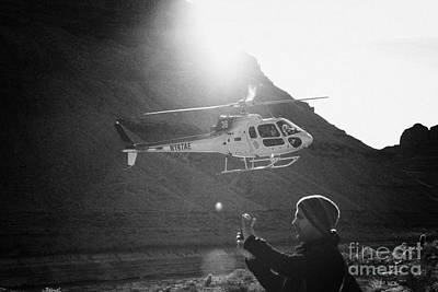 tourist taking photos with smart phone as papillon helicopter tours comes in to land in the Grand ca Art Print by Joe Fox