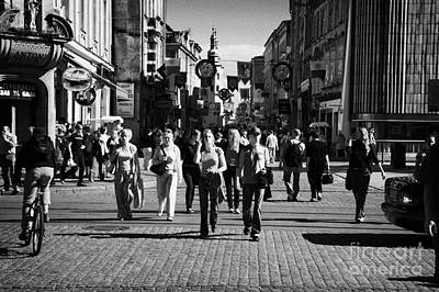 Cracovia Photograph - tourists walking along Grodzka street towards camera and towards main town square in Krakow by Joe Fox