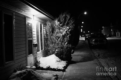 Sask Photograph - Traditional House With Porch Light Outside The Door And Snow Cleared Pavements At Night Delisle Sask by Joe Fox