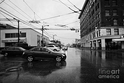 Rainy Day Photograph - traffic at the junction of main and broadway on a wet rainy day Vancouver BC Canada by Joe Fox