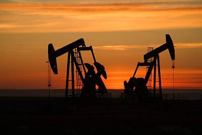 Birds Rights Managed Images - Two pump jacks at dusk Royalty-Free Image by Jeff Swan