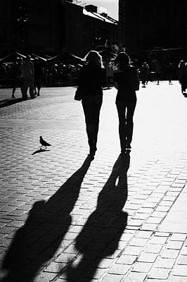 Cracovia Photograph - Two Young Women And Pigeon Cast Long Shadows On Paved Area Of Krakows Rynek Glowny Main Square by Joe Fox