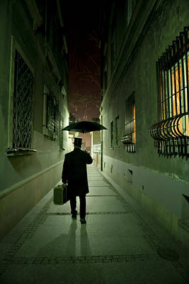 Photograph - Victorian Man With Top Hat Carrying A Suitcase And Umbrella Walking In The Narrow Street At Night by Jaroslaw Blaminsky