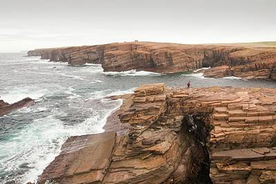 Sea Arch Photograph - Walker Crossing A Sea Arch by Ashley Cooper