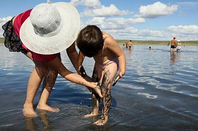 Clay Relief Photograph - Woman And Child In Mud Pool by Science Photo Library