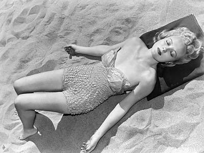 One Piece Swimsuit Photograph - Woman Sun Bathing At The Beach by Underwood Archives