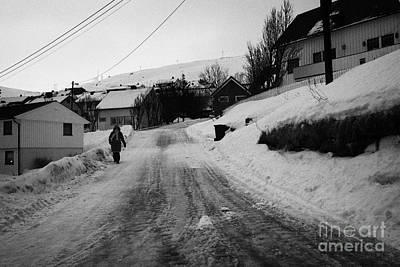 woman walking down steep ice covered street in Honningsvag finnmark norway europe Art Print by Joe Fox