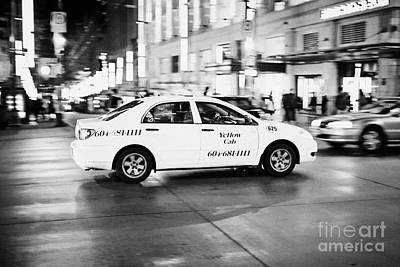yellow cab taxi crossing junction downtown Vancouver city at night BC Canada deliberate motion blur Art Print by Joe Fox