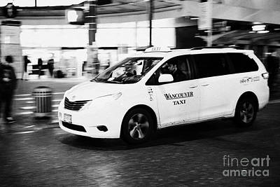 yellow cab taxi downtown Vancouver city shopping area at night BC Canada deliberate motion blur Art Print by Joe Fox