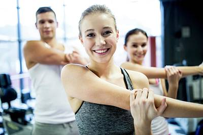 Self-confidence Wall Art - Photograph - Young Adults Doing Warm Up Exercise by Science Photo Library