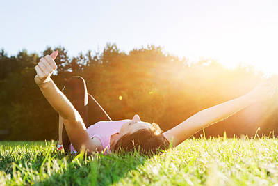 Cheerful Photograph - Young Beautiful Woman Lying Relaxing And Stretching On The Grass by Michal Bednarek
