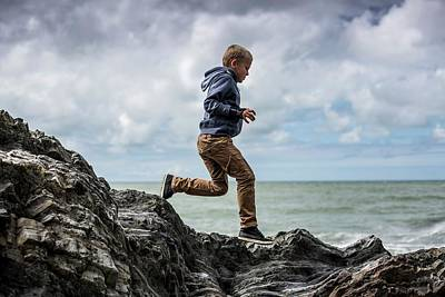 Great Outdoors Photograph - Young Boy Playing On Rocks On Beach by Samuel Ashfield