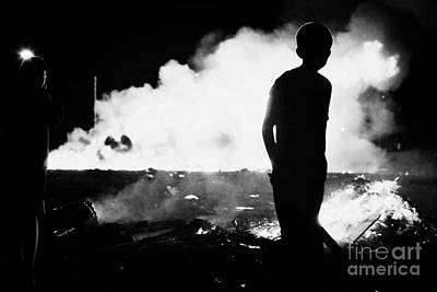 young boy walks past 11th night bonfire in Monkstown fire northern ireland Art Print